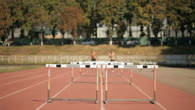 Two sprinters jumping over five hurdles on runways stock video footage