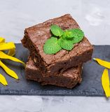 Two square baked piece of brownie pie. On a black board, top view royalty free stock photos