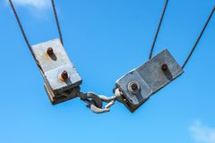 Two square metal blocks and pulleys from a commercial fishing boat fastened together - close-up - against a blue sky stock photo