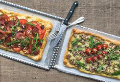 Two square pizzas with fresh arugula and cherry-tomatoes on silv Royalty Free Stock Photo