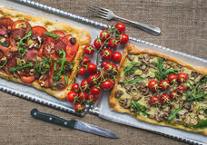 Two square pizzas with fresh arugula and cherry-tomatoes on silv Royalty Free Stock Photography