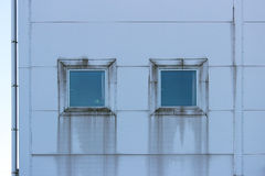 Two square windows with siding imitating steel, on large sports complex.  Royalty Free Stock Photography