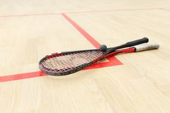 Two squash rackets and ball. On the wooden floor. Racquetball equipment on the court on red lines. Photo with selective focus royalty free stock photo