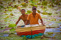 Two Sri Lankan fishermen in a lotus pond Stock Photo