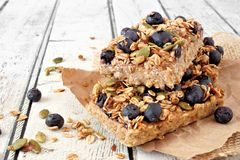 Two stacked superfood breakfast bars, on rustic white wood. Two stacked superfood breakfast bars with oats and blueberries, side view on rustic white wood Royalty Free Stock Photos