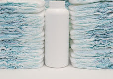 Two stacks of baby diapers and a talc powder bottle Stock Image