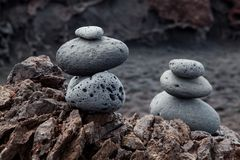 Two stacks of balanced pebbles or cairns on the beach in El Golfo, Lanzarote, Spain. This picture has been taken on a typical volcanic black beach in Lanzarote royalty free stock image