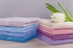 Two stacks of colorful bath towels with hyacinth flower on light Royalty Free Stock Images