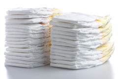 Two Stacks of Diapers. Two aligned stacks of baby disposable nappies over white background royalty free stock photography