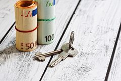 Loan contribution or rental payment concept. Two stacks of european union currency - euro - in fifty and hundred banknotes and a bunch of door keys nearby. Real Royalty Free Stock Photos