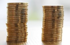 Two stacks of gold money coins coin in pile on blurred background. Two stacks of shiny gold money coins coin in pile on blurred background Stock Photos