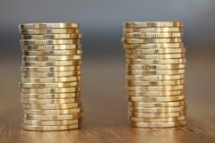 Two stacks of gold money coins coin in pile on blurred background. Two stacks of shiny gold money coins coin in pile on blurred background Royalty Free Stock Images