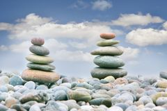 Two stacks of stones over sky background. Two stacks of stones over over sky background, focus on the left one Royalty Free Stock Photography
