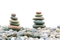 Two stacks of stones over white. Focus on the left one Royalty Free Stock Images
