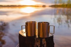 Two stainless steel camping cups or mugs on a wooden stump against a dramatic sunrise or sunshine by a lake. Camping concept. stock photo