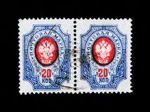 Two stamps printed in Russia shows postage stamp of the Russian Empire with the coat of arms, circa 1911. MOSCOW, RUSSIA - JUNE 26, 2017: Two stamps printed in stock photo