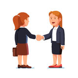 Two standing business woman shaking hands firmly Stock Images