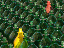 Two standing out. Many green, one yellow and one red plastic bottle stock photos