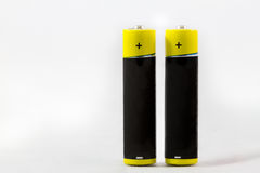 Two standing yellow-black AAA alkaline batteries isolated on whi. Two standing yellow black AAA alkaline batteries isolated on a white background with copy-space Royalty Free Stock Photo