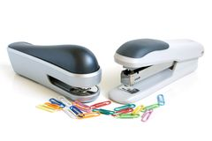 Two staplers and multicolored paper clips Stock Images