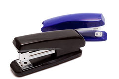 Two staplers on a white background. Black and blue staplers with white background close up Royalty Free Stock Photos