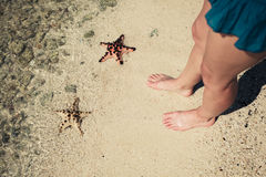 Two starfish and the feet of a young woman Royalty Free Stock Images