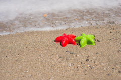 Two starfish-shaped molds on the sand Stock Photos