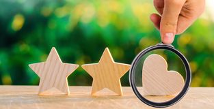 two stars and heart on a green bokeh background. three star rating, the choice of the editorial office and the buyer. concept stock photo