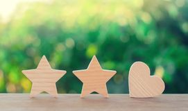Two stars and heart on a green bokeh background. three star rating, the choice of the editorial office and the buyer. concept of r. Ating, review. quality royalty free stock photo