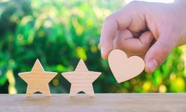 Two stars and heart on a green bokeh background. three star rating, the choice of the editorial office and the buyer. concept of r stock image