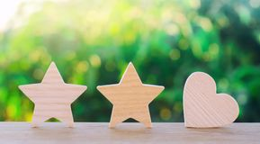 Two stars and heart on a green bokeh background. three star rating, the choice of the editorial office and the buyer. concept of r royalty free stock photos