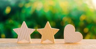 Two stars and heart on a green bokeh background. three star rating, the choice of the editorial office and the buyer. concept of r royalty free stock photography