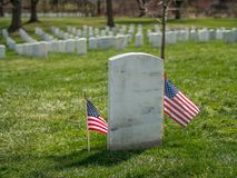 Lonely white grave stone with US Flag at Arlington National Cemetery, Virginia. Two stars and stripes flags enframe a white gravestone at Arlington National Royalty Free Stock Photography
