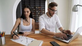 Two start up partners work in workspace at desk. In trendy loft close up with background books. Small business team closing do job in work place. Guy use pc and