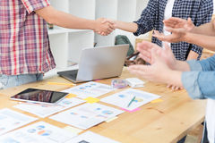 Two start up young people shaking hands after meeting while thei Stock Photo