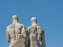 Two statues. From behind in front of a blue sky royalty free stock images