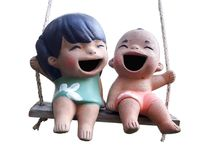 Two statuettes of funny boy and girl. Sitting on rope swing isolated on white background with clipping path Stock Image