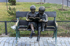 Two statuettes, standing reading on a park bench. Togeter Stock Image
