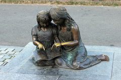 Two statuettes, standing reading on a park. Togeter Royalty Free Stock Image