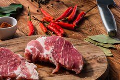 Two steak with chili, cayenne powder and other condiment Royalty Free Stock Photos