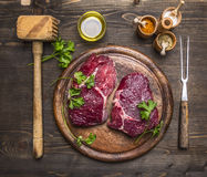 Two steaks on a cutting board with herbs and spices,  hammer for meat and meat fork. Two steaks on a cutting board with herbs and spices, with a hammer for meat Stock Image
