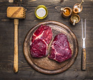 Two steaks on a cutting board with herbs and spices, with  hammer for meat and meat fork Royalty Free Stock Photography