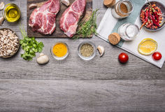 Two steaks with oil and spices on cutting board  with lemon, salt and meat fork, sliced mushrooms, napkin border ,with text area o Stock Image