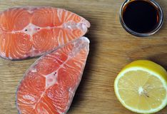 Two steaks of red fish with lemon and soy sauce. On a wooden board Royalty Free Stock Photography