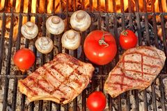 Two Steaks and Vegetables Char-Grilled Over Flaming BBQ Grill Royalty Free Stock Images