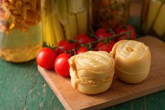 Two steamed rolled cheeses on green table. Photo of one Parenica rolled steamed cheese on wooden board which is placed on another wooden table with tomatoes near Royalty Free Stock Photo