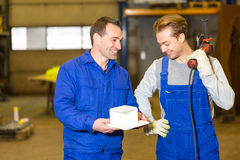Two steel construction workers inspecting metal pieces Stock Photos