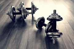 Two steel dumbbells on a wooden floor. Steel dumbbells are ready for training royalty free stock photo