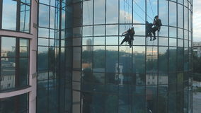 Two steeplejacks are cleaning the windows of the business center. The man and woman steeplejacks wearing the outfit hang near the glass building. Professional stock footage