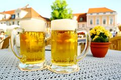 Two steins beer garden in the city. Soft focus stock images